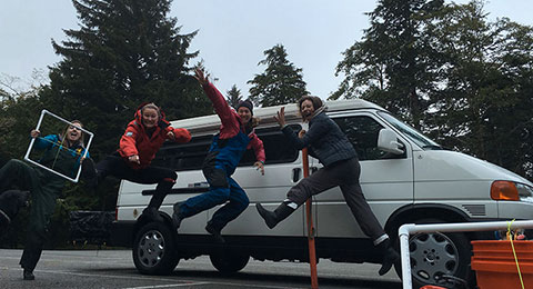 photo of a scholars jumping in front of a white van